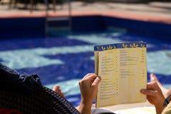 旅游看食物菜单在游泳池周围旁边在一家旅馆里在果阿,印度 免版税库存照片