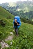 旅游背包徒步旅行者的山 免版税库存照片
