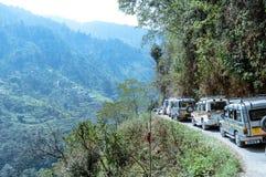 旅游车在喜马拉雅山谷的步小山区域排列上升 免版税库存图片