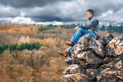 旅游远足者坐在山的岩石 免版税库存照片