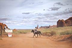 旅游骑乘马在纳瓦霍族保留地的纪念碑谷公园 库存照片