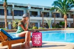 旅行、夏天休假和假期概念-走在旅馆带着红色手提箱的游泳池周围附近的美女在埃及 库存图片