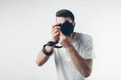 旅行、技术和生活方式概念:拍与数字照相机的年轻有胡子的摄影师照片 免版税库存图片