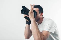 旅行、技术和生活方式概念:拍与数字照相机的年轻有胡子的摄影师照片 免版税库存照片