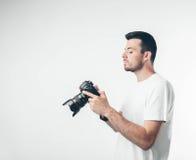 旅行、技术和生活方式概念:拍与数字照相机的年轻有胡子的摄影师照片 图库摄影