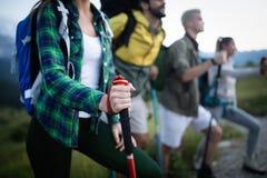 旅行、旅游业、远足、姿态和人概念-小组有背包的微笑的朋友 免版税库存图片