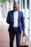 旅行与袋子和手机的非洲商人 免版税库存照片