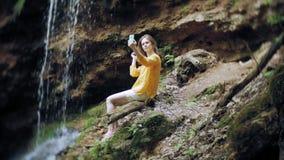 旅行为在山瀑布的冒险妇女一个智能手机照相,享受自然美好的风景  影视素材