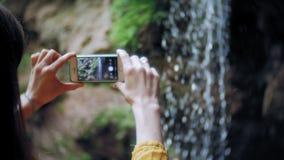 旅行为在山瀑布的冒险妇女一个智能手机照相,享受自然美好的风景  股票录像