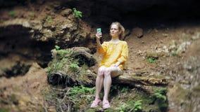 旅行为在山瀑布的冒险妇女一个智能手机照相,享受自然美好的风景  股票视频