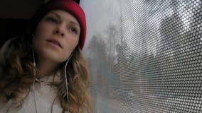 旅行乘公共汽车的年轻快乐的妇女在一哀伤的天 她看窗口 股票录像
