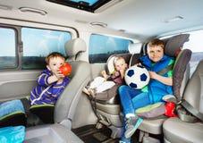旅行乘在安全位子的汽车的逗人喜爱的小男孩 免版税库存照片