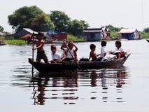 旅行乘小船的小组孩子在浮动村庄 免版税库存照片
