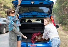 旅行乘带着手提箱的汽车的母亲和女儿 免版税图库摄影