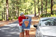 旅行乘汽车的夫妇在森林里 图库摄影