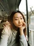 旅行乘火车或公共汽车,坐在窗口附近和采取selfie -享受的年轻俏丽的亚裔妇女旅行 库存照片