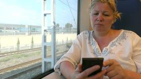 旅行乘火车的妇女 电话联系 库存图片