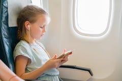 旅行乘飞机的可爱的小女孩 与膝上型计算机的逗人喜爱的孩子在航空器的窗口附近 免版税图库摄影