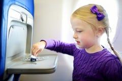 旅行乘飞机的可爱的小女孩 坐由航空器窗口和使用与玩具飞机的孩子 旅行与孩子 免版税库存图片