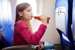 旅行乘飞机的可爱的小女孩 坐由航空器窗口和喝饮料的孩子 库存图片