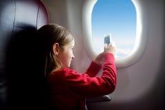 旅行乘飞机的可爱的小女孩 坐由航空器窗口的孩子为天空照相 免版税库存照片