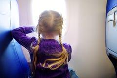 旅行乘飞机的可爱的小女孩 看的孩子坐由航空器窗口和外面 旅行与孩子 库存图片