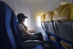 旅行乘飞机的妇女 看的妇女坐由航空器窗口和外面 库存图片