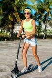 旅行乘滑行车的妇女 scootering在海滩的愉快的性感的妇女反撞力在棕榈附近在热带国家 免版税库存照片