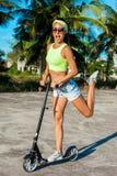 旅行乘滑行车的妇女 scootering在海滩的愉快的性感的妇女反撞力在棕榈附近在热带国家 库存图片