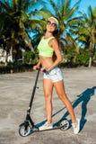 旅行乘滑行车的微笑的妇女 scootering在海滩的愉快的被晒黑的妇女在棕榈附近在热带国家 免版税库存图片