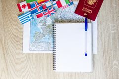 旅行准备:护照,路线图,开放笔记本,在木桌上的国旗 假期计划概念 免版税图库摄影
