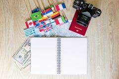 旅行准备:金钱,护照,路线图,减速火箭的影片照相机,在木桌上的开放笔记本 库存照片