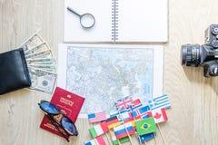旅行准备:金钱,护照,路线图,太阳镜,放大镜,减速火箭的影片照相机,在木桌上的笔记本 免版税图库摄影