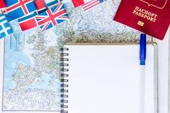 旅行准备:金钱,护照,路线图,开放笔记本,在木桌上的国旗 假期计划 图库摄影