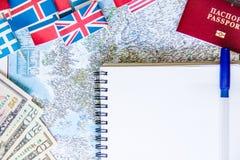 旅行准备:金钱,护照,路线图,开放笔记本,在木桌上的国旗 假期计划 库存图片