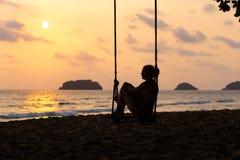 旅行博克照片:一名妇女的剪影一件礼服的在日落期间有在海的一个看法有在天际的一小isand的 库存图片