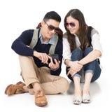 旅行和使用手机的亚洲年轻夫妇 免版税库存照片
