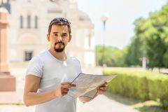 旅行和假期概念:有纸地图的可爱的成年男性游人在城市广场或街道在好日子 r 免版税库存照片