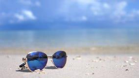 旅行和假期概念 在一个白色海洋海滩的蓝色太阳镜 Lazure绿松石海在与拷贝的背景中 股票录像