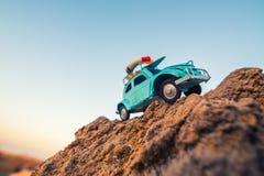 旅行和冒险:在岩石的玩具减速火箭的汽车 免版税库存照片