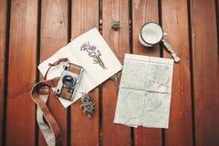 旅行和旅行癖舱内甲板位置 照片照相机,地图,笔记本,杯子顶视图,会集了在木土气背景的野花 库存图片