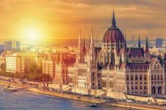旅行和欧洲旅游业概念 议会和河沿在有观光的船的布达佩斯匈牙利在夏日日落期间 免版税库存图片