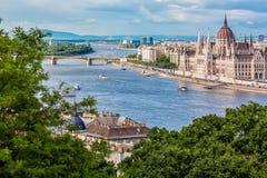 旅行和欧洲旅游业概念 在夏天晴天w期间,议会和河沿在有观光的船的布达佩斯匈牙利 免版税库存图片