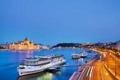 旅行和欧洲旅游业概念 议会和河沿在有观光的船的布达佩斯匈牙利在蓝色小时日落期间 库存照片