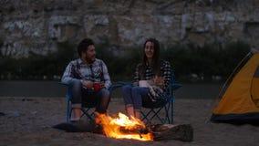 旅行和爱概念 在壁炉附近的年轻可爱的夫妇在阵营 股票视频