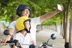 旅行和采取在摩托车的父亲和女儿selfie 库存图片