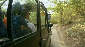 旅行在一条土路的森林里在军事SUV 股票视频