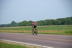 旅行在乡下公路的自行车骑士 免版税库存照片