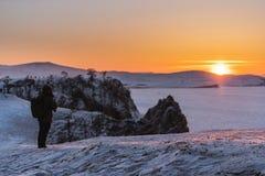 旅行在冬天在贝加尔湖在伊尔库次克,俄罗斯 在日落的冬天风景与享用美丽的太阳的年轻摄影师 免版税库存照片