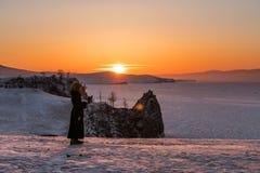 旅行在冬天在贝加尔湖在伊尔库次克,俄罗斯 在日落的冬天风景与使用流动巧妙的电话和e的少妇 库存图片
